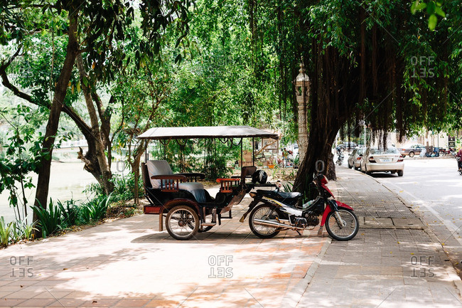 Cambodia - June 7, 2015: Motorcycle taxi parked on a sidewalk in Cambodia