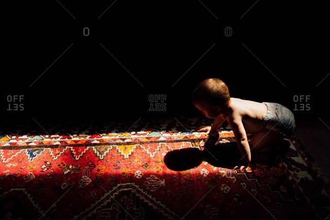 Toddler crawling on rug in sunlight