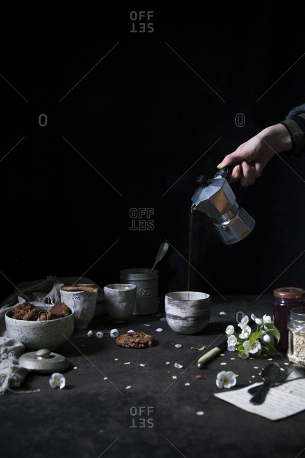 A person pouring coffee into a cup from a moka pot on a breakfast table on a dark background