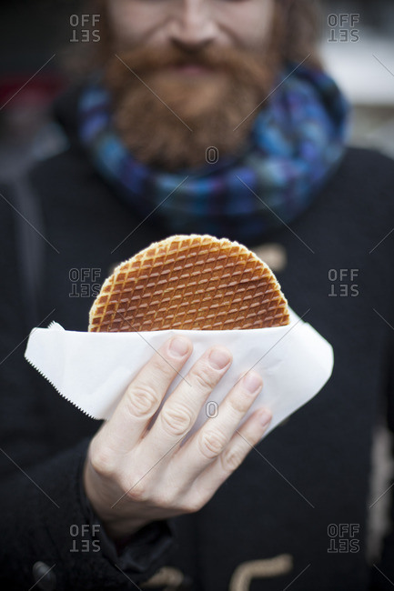 A man with red beard is holding a dutch stroopwafel
