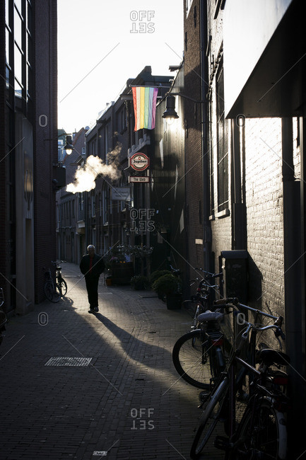 A man walking in a quaint alleyway of Amsterdam, The Netherlands