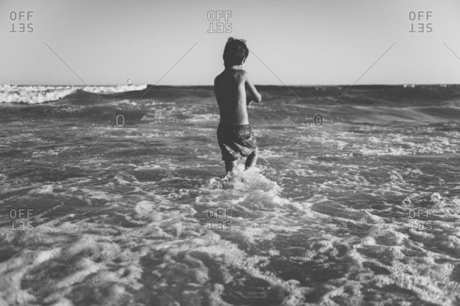 Boy wading out in the sea