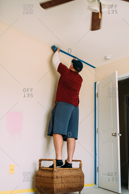 Man taping edges of a wall with painter's tape