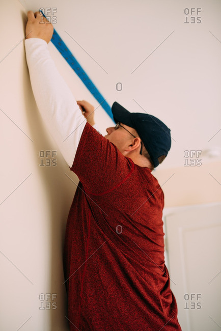 Man taping ceiling edges with painter's tape