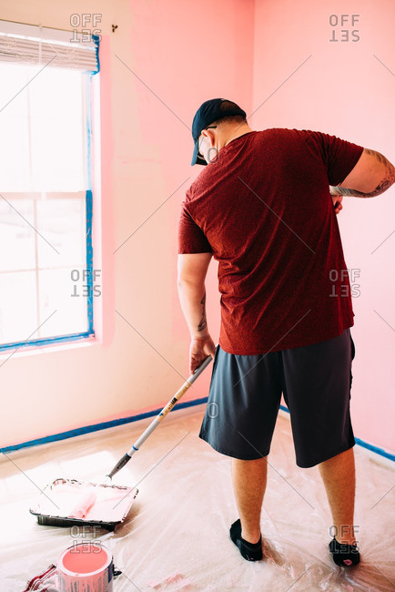 Man dipping a roller into pink paint