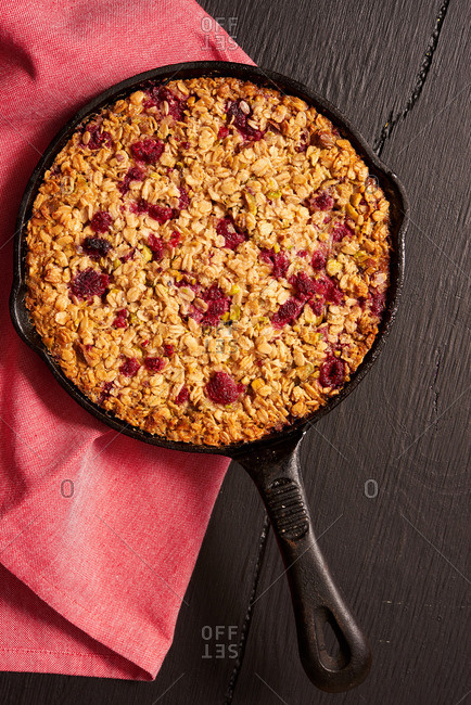 A berry oatmeal crisp served in cast-iron cookware