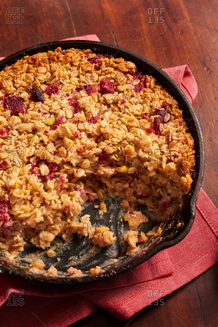 Serving of berry oatmeal crisp missing from a cast-iron skillet