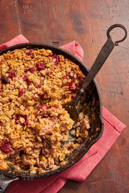 Serving spoon in a cast-iron skillet of berry oatmeal crisp