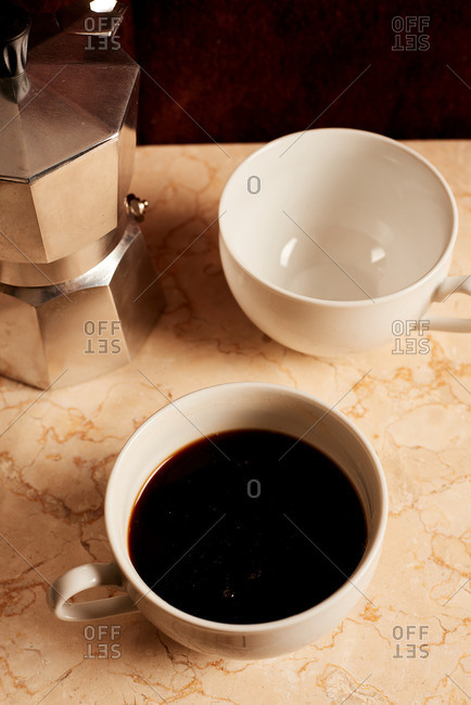 Stovetop espresso maker next to two cups of coffee