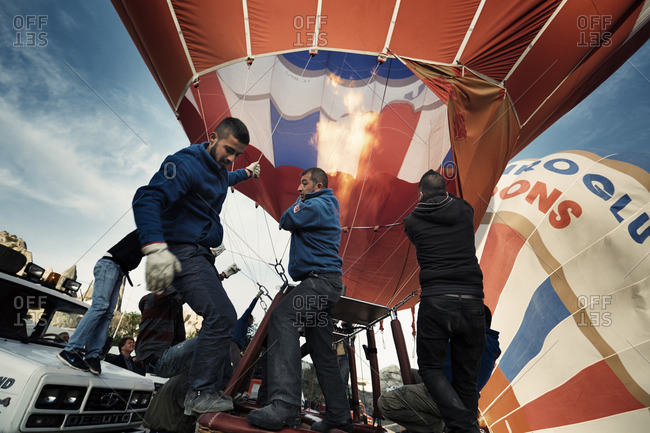 Cappadocia, Turkey - May 04, 2014: People prepare a hot air balloons in Cappadocia area known around the world as one of the best places to fly with hot air balloons