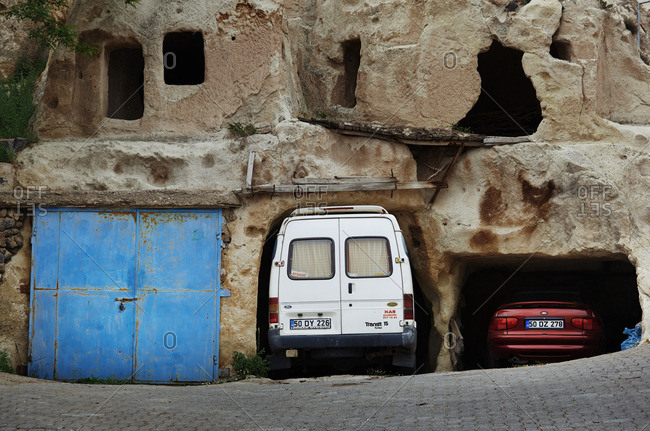 Cappadocia, Turkey - May 06, 2014: Cars parked inside the rock formations with natural eroded caves