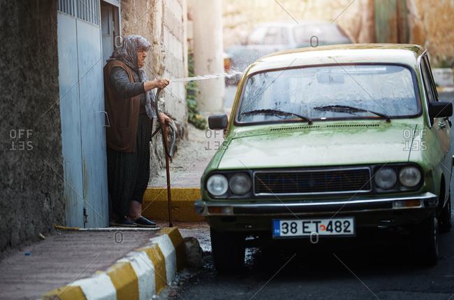 Cappadocia, Turkey - May 07, 2014: Senior Turkish woman washing car