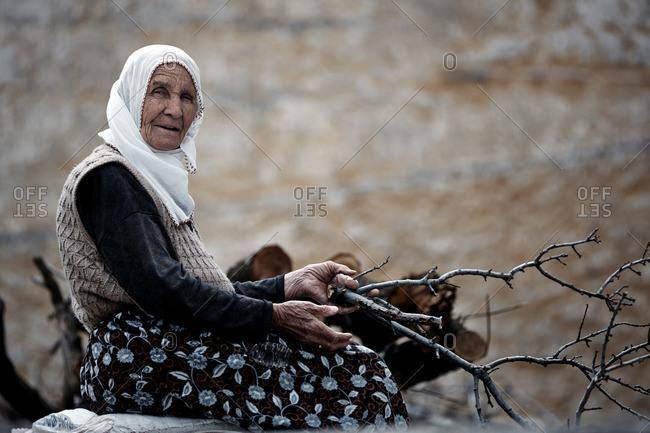Cappadocia, Turkey - May 07, 2014: Senior Turkish woman preparing firewood
