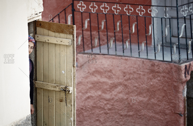 Cappadocia, Turkey - May 07, 2014: Ashamed adult Turkish woman looking at camera through the door