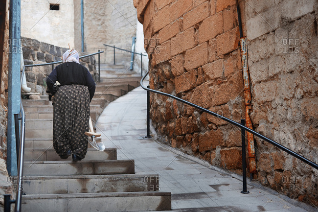 Senior Turkish woman going by staircase and carrying shovel