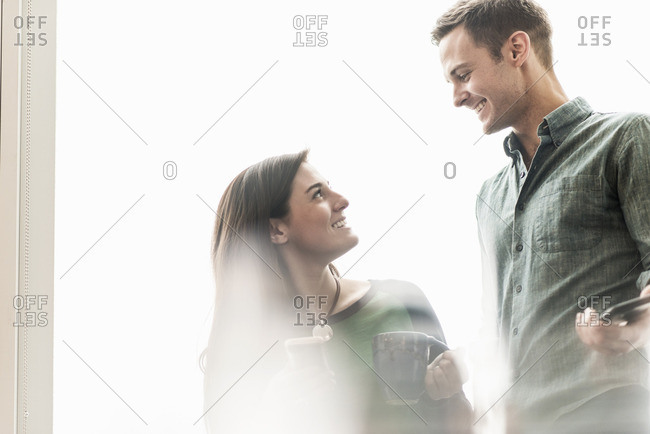 A man and woman talking in an office over coffee