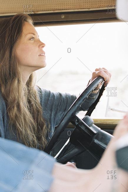 Barefoot woman resting her feet on the dashboard of a 4x4, a tattoo on her right foot, another woman driving