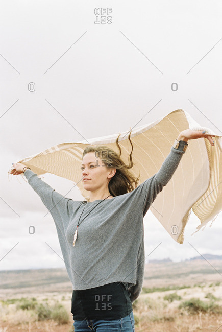 Woman standing in a desert with her arms raised, holding a wrap which is fluttering in the wind