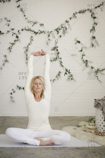 A blonde woman in a white leotard and leggings, sitting on a white mat in a room stretching her arms A creeper plant on the wall behind her