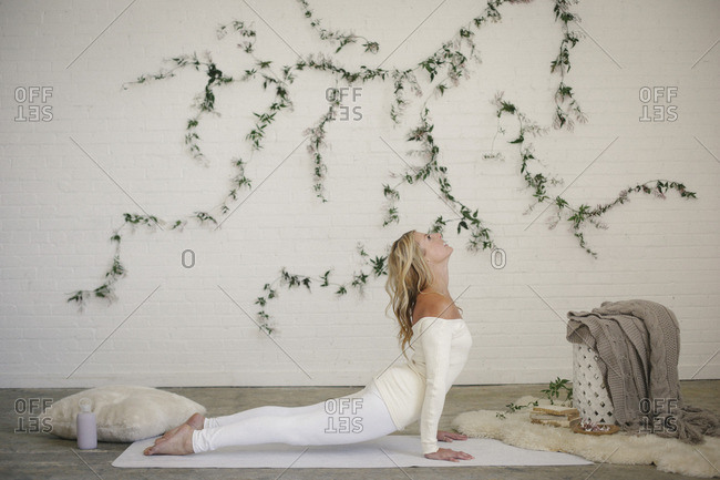 A blonde woman in a white leotard and leggings, lying on a white mat in a room, arching he back in a stretch