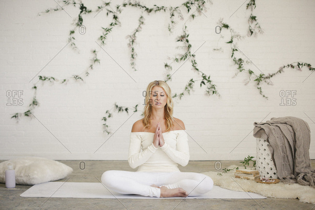 A blonde woman in a white leotard and leggings, sitting on a white mat in a room, doing yoga A creeper plant on the wall behind her