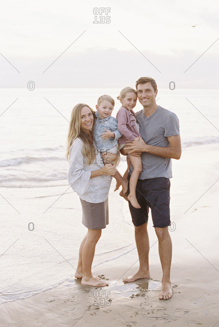 Couple standing with their son and daughter on a sandy beach by the ocean, looking at camera, smiling