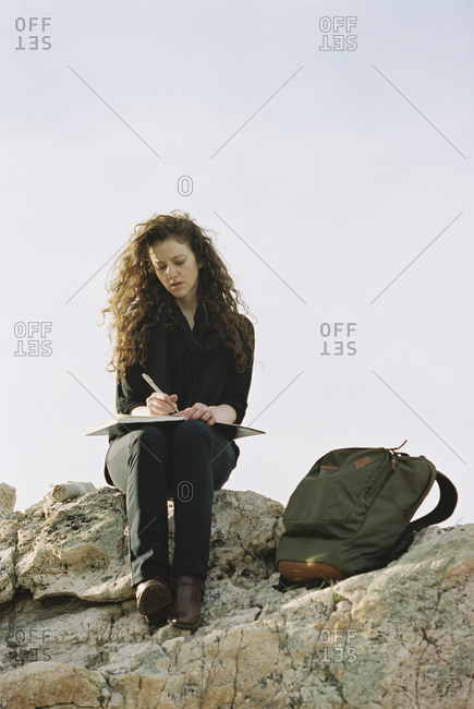 A woman sitting on a rock, writing in a notebook, a backpack lying by her feet