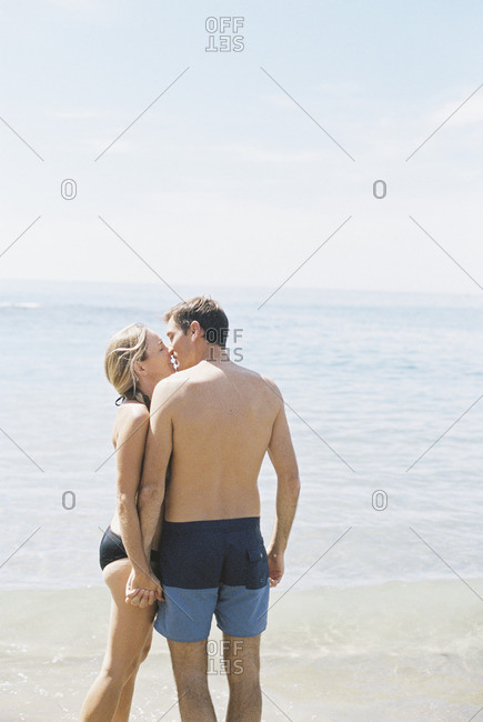 Couple in swimwear standing on a sandy beach by the ocean, kissing