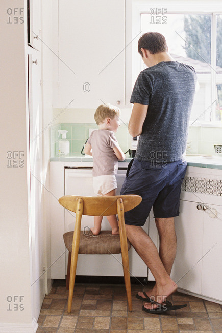 Man standing in a kitchen, his son standing on a chair beside him
