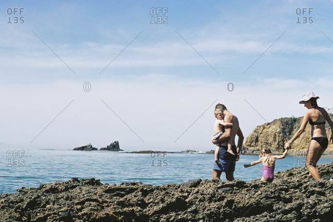 A family on holiday, two adults with their son and daughter walking across rocks by the ocean
