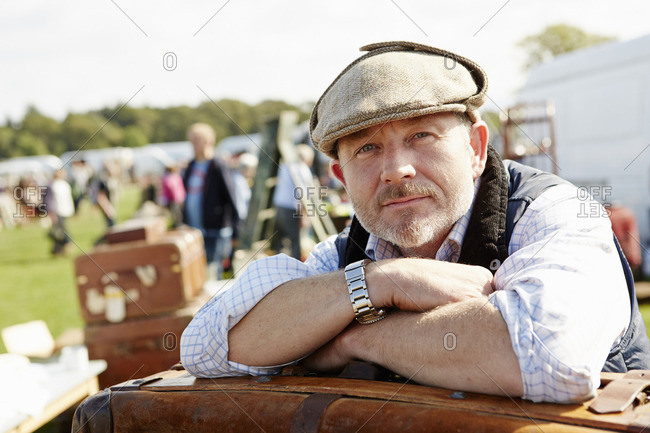 Smiling man wearing a flat cap at a flea market, a trader resting leaning on a pile of cases