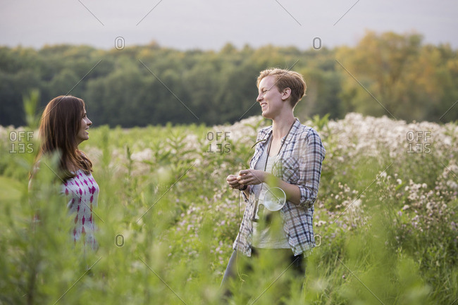Two women standing in a meadow surrounded by tall grass and wild flowers