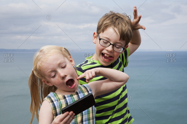 Brother and sister making faces and taking a selfie with a smart phone