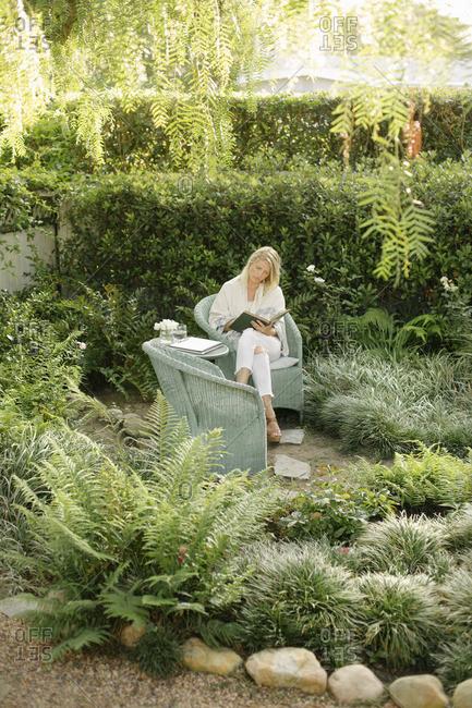 Blond woman sitting in a wicker chair in a garden, reading