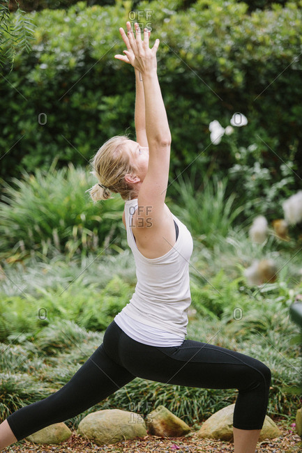 Blond woman doing yoga in a garden