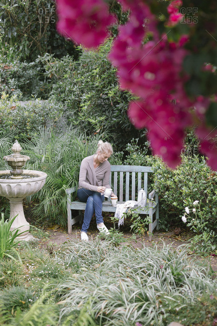Woman sitting on a wooden bench in a garden, taking a break