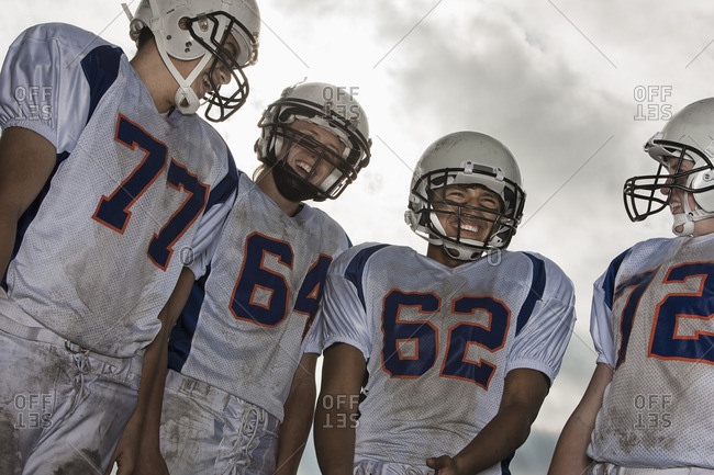 A group of football players, members of a squad, young people in sports uniform and protective helmets, heads and shoulders