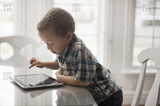 A young child sitting at a table using a digital tablet with a touchscreen