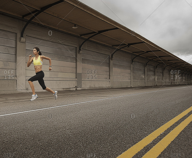 A woman running along an urban road, arms working and legs striding out