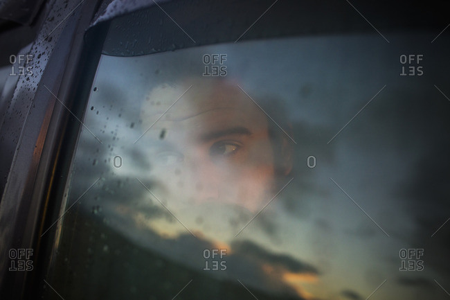 A man sitting in a car looking out Reflections of the sunset sky on the window