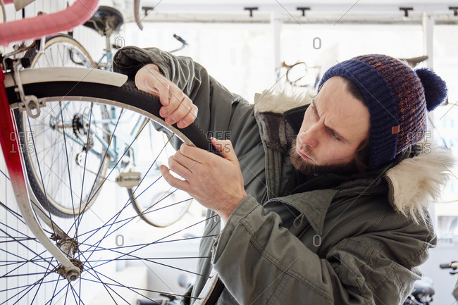 A young man working in a cycle shop, repairing a bicycle