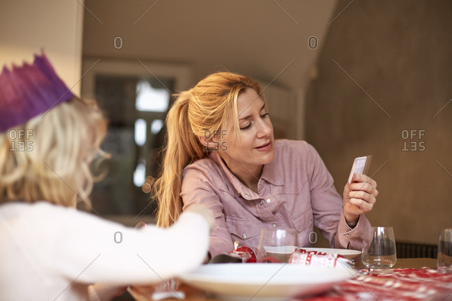 A woman and a child seated at a kitchen table sharing a cracker joke