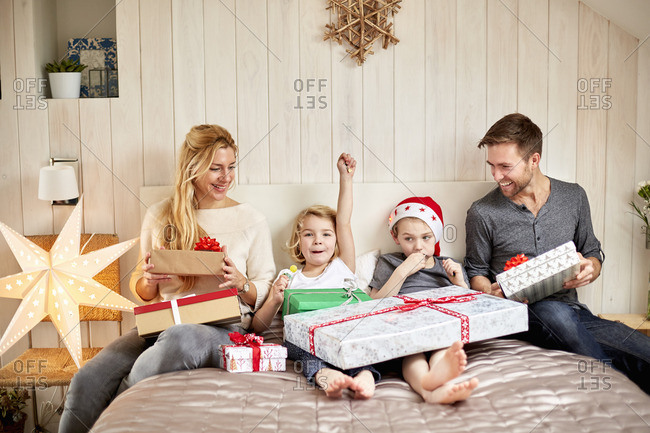 A family, two adults and two children sitting in bed on Christmas morning opening presents together