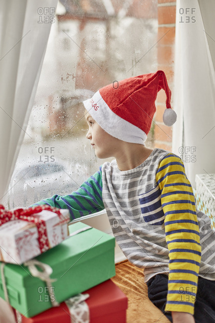 Christmas morning in a family home A boy in a Santa hat looking out of a bedroom window