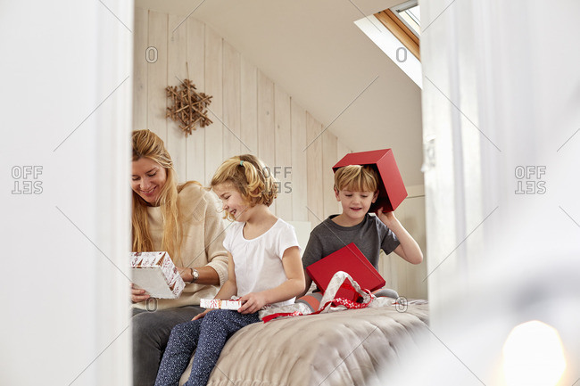 Christmas morning in a family home A mother and two children sitting on a bed opening presents