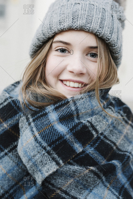 A young girl in a tartan plaid shawl and woolly hat outdoors in the winter