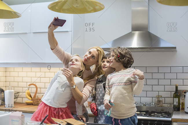 An adult woman and three children taking a selfie photograph in the kitchen