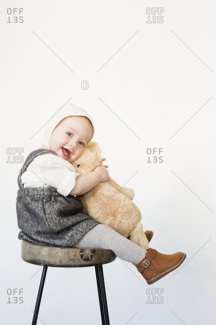 A young child, a girl sitting on a tall stool holding a teddy bear