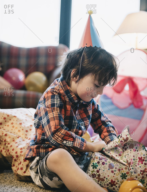 A boy unwrapping his presents at his birthday party