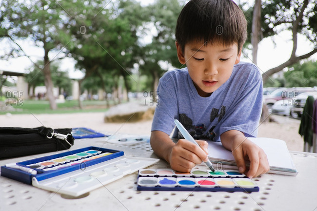 Boy painting outdoors with watercolors